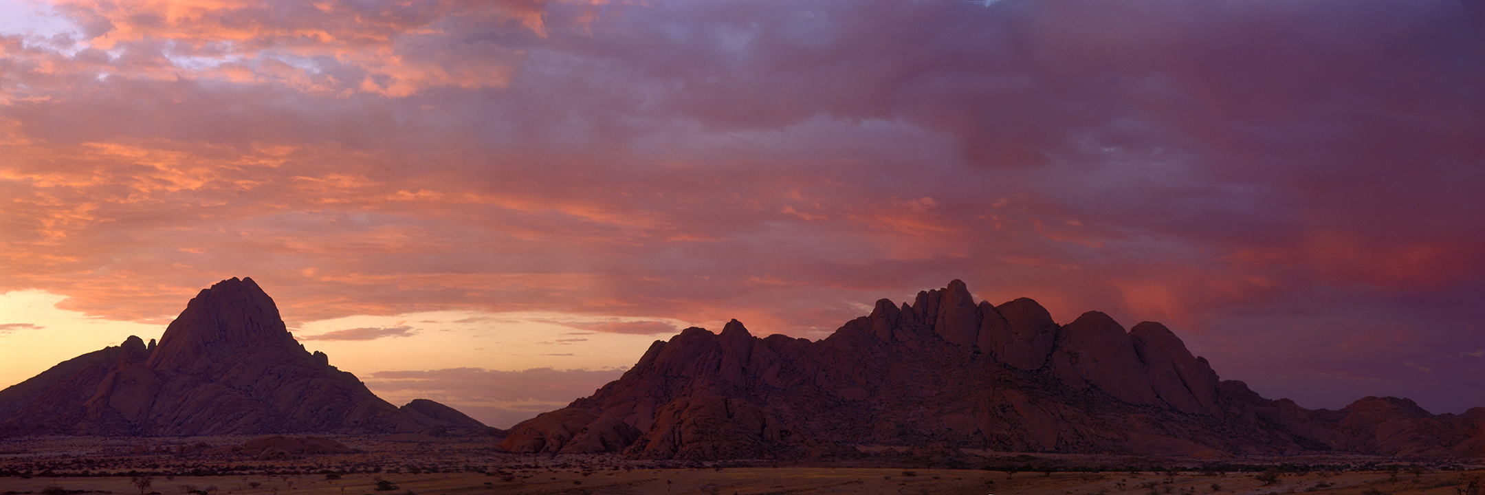 Inselberg Spitzkoppe bei Sonnenaufgang mit rot glühenden Wolken, Namibia - island mountain mount spitzkoppe at sunrise with red glowing clouds, namibia